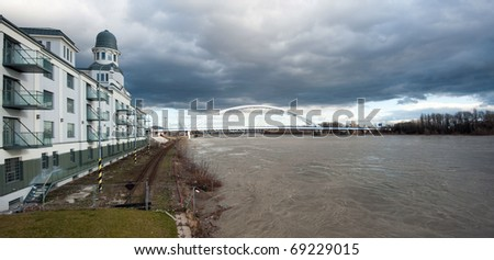 high water level on river Danube, dark clouds in background, Bratislava, Slovakia
