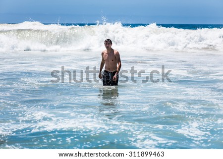 High waves approaching to young man in ocean