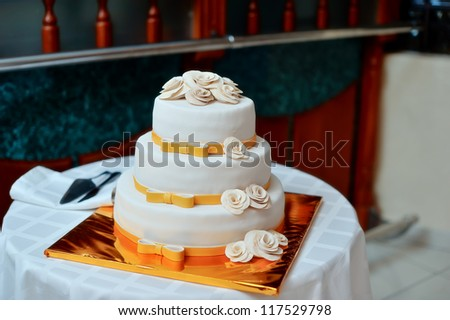 high white wedding cake with beautiful flowers on a golden pedestal - stock photo