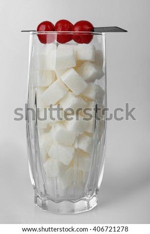 Highball glass with lump sugar and cocktail cherries on grey background - stock photo