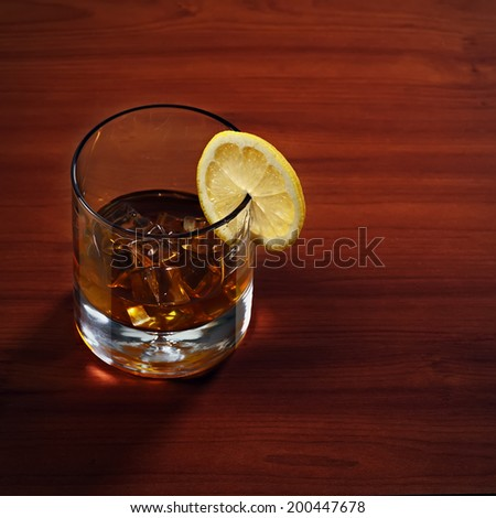 Highball whiskey glass with ice and lemon on wooden background. Closeup.