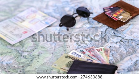 Higher contrast composition on travel topic.  Unfolded detailed topographic map exotic Asian cash notes credit cards sunglasses passport entry stamps many - stock photo