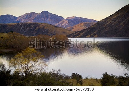 Highland lake with last patches of light giving pastel colours on nearby hills - stock photo