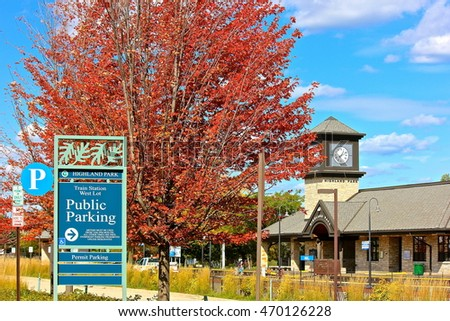 Highland Park, IL, USA - October 5, 2014: A colorful sunny autumn afternoon view of fall red leaves, blue sky, a clock tower and signage at a Midwest USA commuter train station.