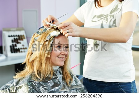 Highlight. Hairdresser woman making highlighting coloring of female client hair in beauty parlour hairdressing salon - stock photo
