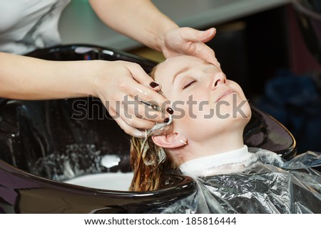Highlight. Washing woman client hair in beauty parlour hairdressing salon - stock photo