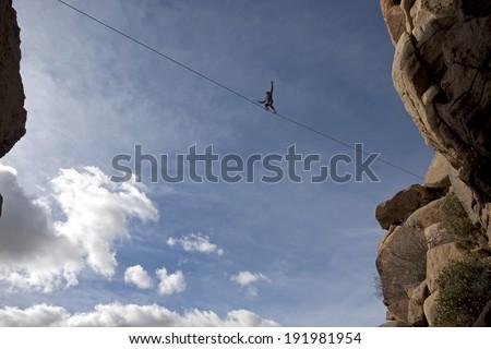 Highline walker in blue sky, Joshua Tree National Park - stock photo