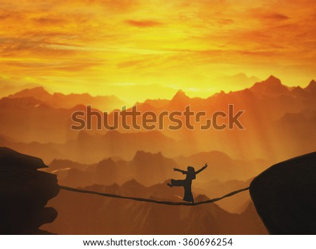 Highline walker silhouette in mountains at sunset Concept of business, challenge, risk taking,concentration - stock photo