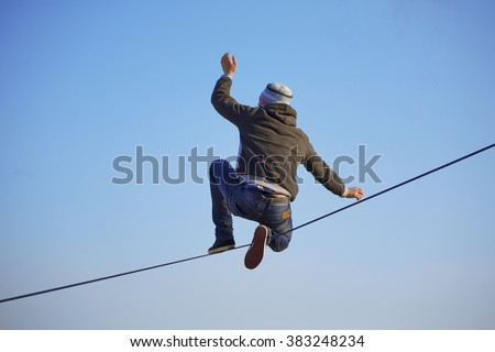 Highliner sitting on one knee on the tight rope on blue sky background, trying to stand up and go - stock photo