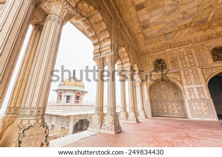 """Highly decorated marble interior of Diwan-e-Khas, """"The Hall of Private Audiences"""" at Agra Fort. The octagonal tower of Musamman Burj can be seen through the cusped arch. - stock photo"""