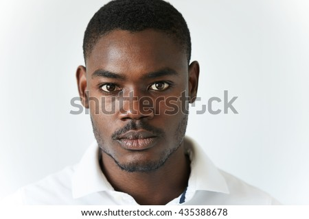 Highly-detailed close up portrait of handsome young African American man wearing stylish polo shirt, looking at the camera with serious thoughtful expression. Human face expression and emotions - stock photo