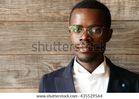 Highly detailed close up portrait of young smart successful African businessman wearing elegant suit and spectacles looking at the camera with serious and confident expression against wooden wall - stock photo