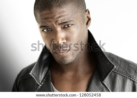 Highly detailed closeup portrait of a tough looking stylish man against white background - stock photo