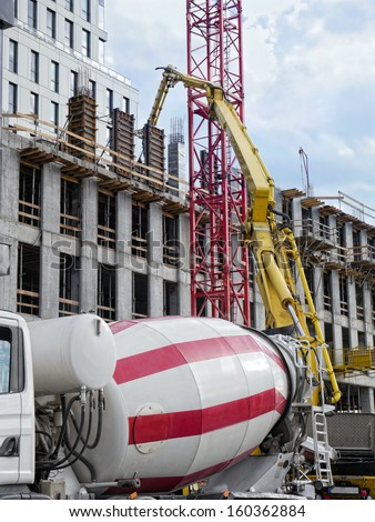 Highrise building under construction and ready mix concrete pump delivering concrete up above - stock photo