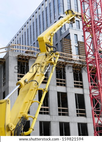 Highrise buildings under construction and yellow ready mix concrete pump delivering concrete up above - stock photo