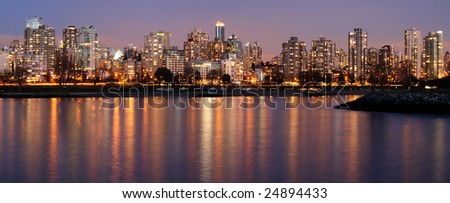 Highrises glow in gathering dusk on a winter Vancouver evening by the English Bay - stock photo