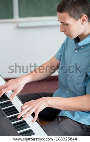 Highschool boy playing piano in schoolroom - stock photo