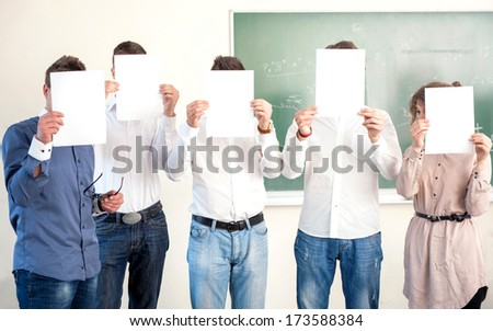 Highschool students holding sheets of blank paper in front of heads - stock photo