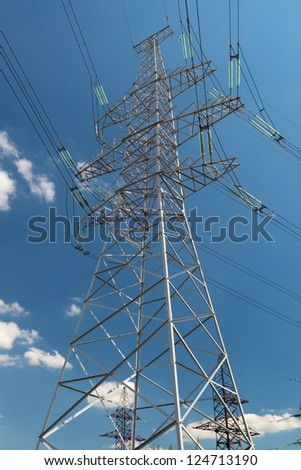 hight voltage line on the blue sky and green grass - stock photo
