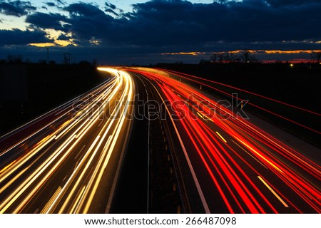 Highway at night in long exposure with traffic - stock photo