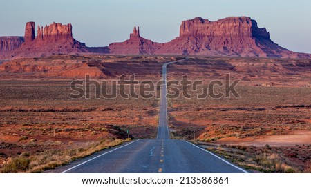 Highway 163 descending into Monument Valley, Utah / Arizona border. The massive distant buttes of Monument Valley are approximately 1000' tall, roughly the height of a 100-story building. - stock photo