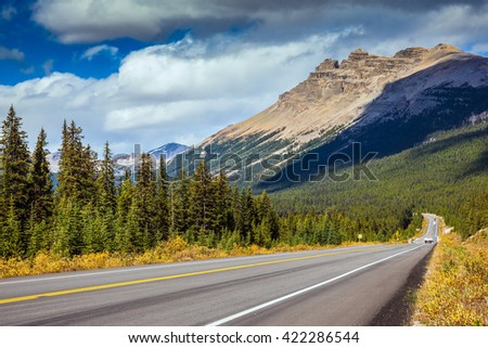 Highway in Banff National Park. Rocky Mountains. Mountains and colorful autumn forest illuminated by the sunset - stock photo