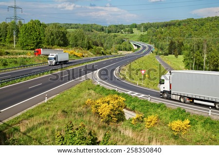 Highway in the countryside. Three moving trucks. Electronic toll gate and a bridge in the distance. View from above. - stock photo