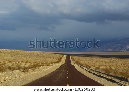 Highway into the darkness, Death Valley, California - stock photo