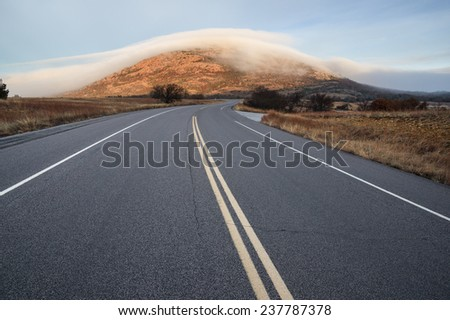 Highway 49 leads towards Mount Scott covered in fog in the Wichita Wildlife Refuge  - stock photo