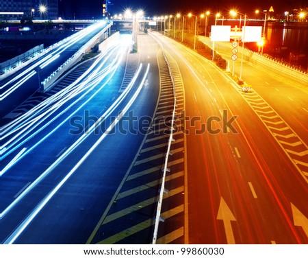 Highway light trails, modern city at night. - stock photo