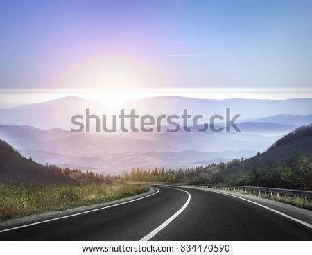 Highway road against mountains and a sky at the sunrise or sunset. - stock photo