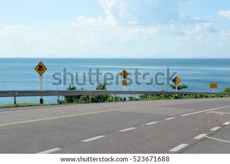 Highway road goes down in mountains to Mediterranean Sea in a sunny day