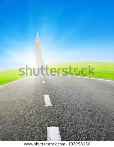 highway road going up as an arrow over green field and blue sky