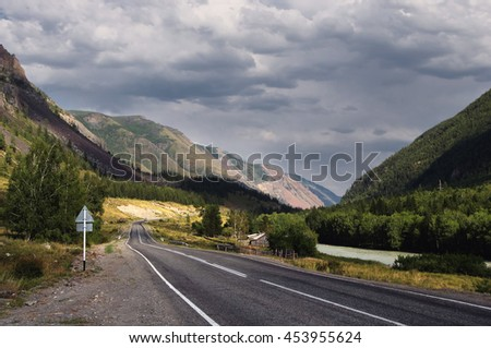 Highway road in a narrow mountain valley along the river, woodland and farm at sunset under a cloudy sky with blue clouds Chuyskiy trakt Altai, Siberia, Russia - stock photo