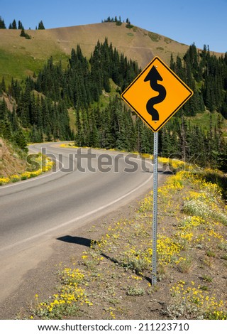 Highway Road Sign Indicates Curves Ahead Mountain Landscape - stock photo