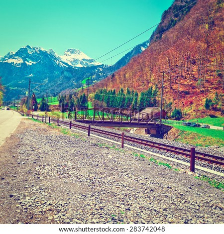 Highway Running Parallel to the Railroad on the Background of Snow-capped Alps in Switzerland, Instagram Effect - stock photo