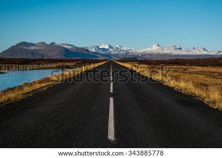 Highway Straight Road and snow capped mountains