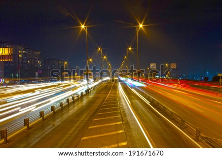 Highway through city at night. Busy light trail traffic on a freeway of Istanbul.  - stock photo