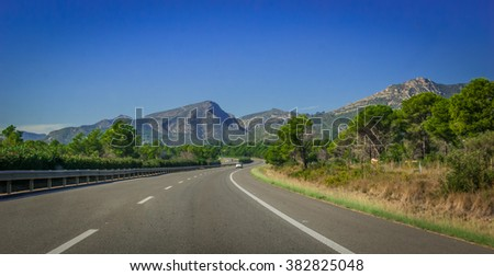 Highway through coastal Foothills and mountains of Spain.  Sunshine on Coastal highway running through foothills and mountain ranges on the edges of continental Europe in Spain.