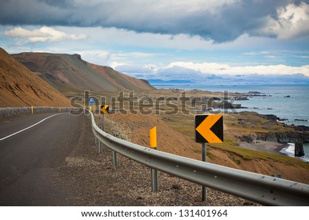 Highway through dry gravel mountains at sea coastline of East Iceland. - stock photo