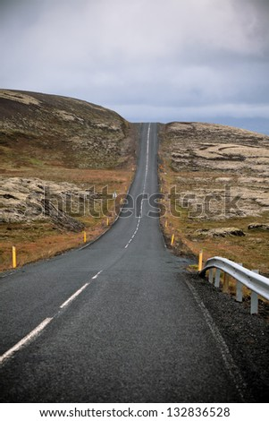 Highway through Iceland Mountain landscape at overcast day. Vertical shot - stock photo