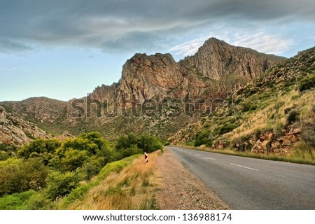 Highway to mountains in dusk. Shot in Montagu, Western Cape, South Africa.  - stock photo