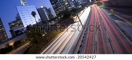 Highway traffic through Los Angeles business district - stock photo