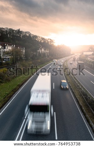 Highway trafic at sunset. Road transportation. Heavy traffic on freeway.