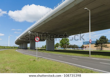 highway viaduct with speed limit traffic shield under it