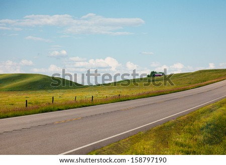 highway with a barn in the background - stock photo