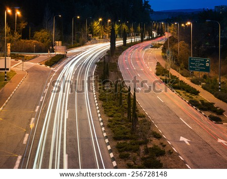 Highway with car traces at night - stock photo