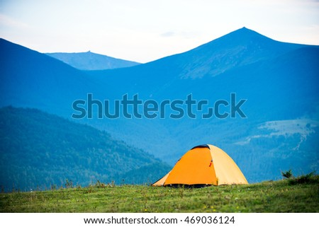 hike yellow tent on the background of mountains, daytime, space