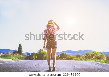 Hiker - A young hiker is walking on the road during her trip - caucasian people - people, nature and lifestyle concept - stock photo