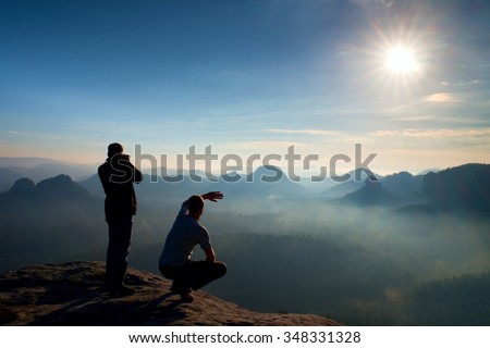 Hiker and photo enthusiast stay on cliff and thinking. Dreamy fogy landscape, blue misty sunrise in a beautiful valley below - stock photo